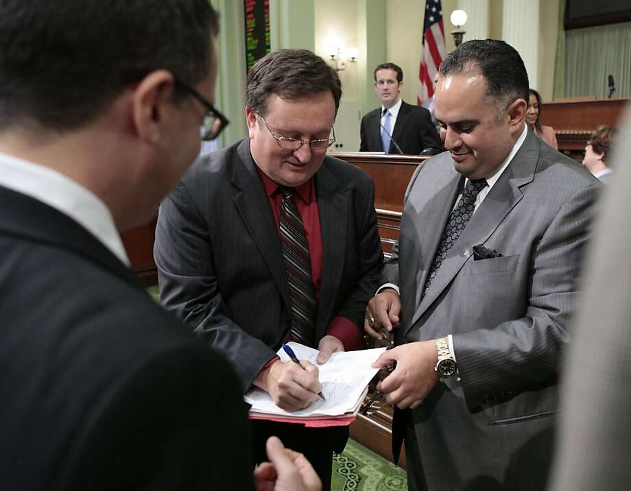 Assemblyman Kevin Jeffries, left, signs a copy of the budget vote for Assembly Speaker John Perez, right, after the Assembly passed the 2012-13 spending plan on a 50-25 at the Capitol in Sacramento in June.  The state of California faces just a $1.9 billion budget gap next year. Photo: Rich Pedroncelli, Associated Press