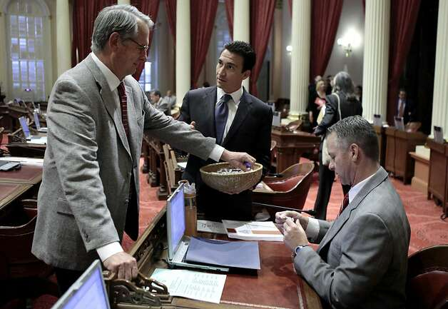 State Sen. Michael Rubio, D-Bakesfield, center, passes out candy to Senators Bill Emmerson, R-Hemet, left, and Anthony Cannella, R-Ceres, before the start of the Senate session at the state Capitol in Sacramento, Calif. Both houses of the Legislature approved the 2012-13 state budget and sent it to the governor. (AP Photo/Rich Pedroncelli) Photo: Rich Pedroncelli, Associated Press