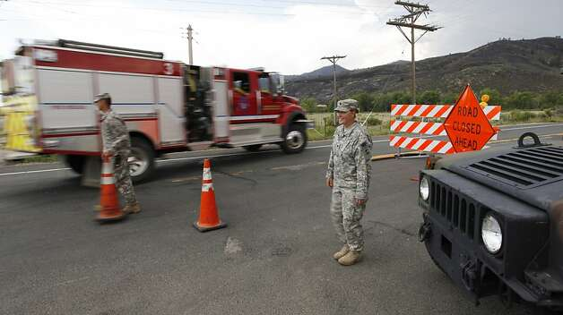 Army National Guardsmen Spc. Rachel Cornett, right, and Sgt. Timothy Apodaca let a fire truck pass their road block leading to the Poudre Canyon on  the High Park wildfire west of Fort Collins, Colo., on Friday,  June 15, 2012. The wildfire started Saturday and has burned over 50,000 acres.   (AP Photo/Ed Andrieski) Photo: Ed Andrieski, Associated Press