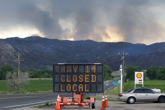 A sign warns motorist of the closure of Highway 14 through Poudre Canyon as columns of smoke rise in the distance from the High Park wildfire west of Fort Collins, Colo., on Friday,  June 15, 2012. The wildfire started Saturday and has burned over 50,000 acres. (AP Photo/Ed Andrieski) Photo: Ed Andrieski, Associated Press