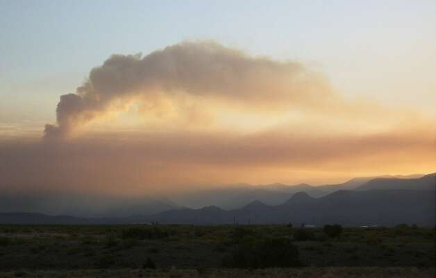 A plume of smoke rises above the Gila National Forest in New Mexico at sunrise, in this photo made on Wednesday, June 13, 2012, and made available Friday by the U.S. Forest Service.  The fire, the largest in state history, burned more than 278,708 acres. (AP Photo/U.S. Forest Service, Marge Williams) Photo: Marge Williams, Associated Press