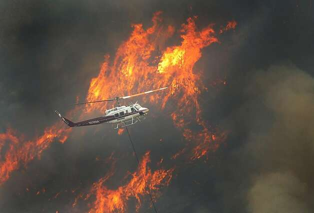 A helicopter flew through the Cache La Poudre Canyon, Colo. as flames scorched the forest south of the river on Thursday, June 14, 2012.  Flames crossed over the Poudre River causing a mandatory evacuation for residents of the Glacier View area. (AP Photo/The Denver Post, Karl Gehring)  MAGS OUT; TV OUT; INTERNET OUT Photo: Karl Gehring, Associated Press