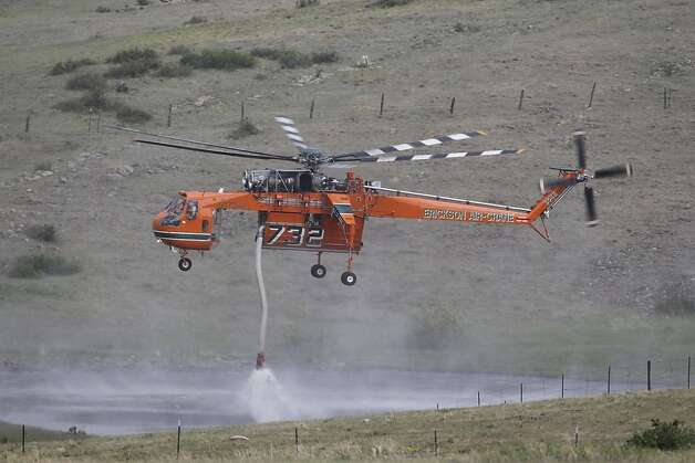 A Erickson Air Crane firefighting helicopter refills its tank in a rancher's pond while fighting  the High Park wildfire west of Fort Collins, Colo., on Friday,  June 15, 2012. The wildfire started Saturday and has burned over 50,000 acres. (AP Photo/Ed Andrieski) Photo: Ed Andrieski, Associated Press
