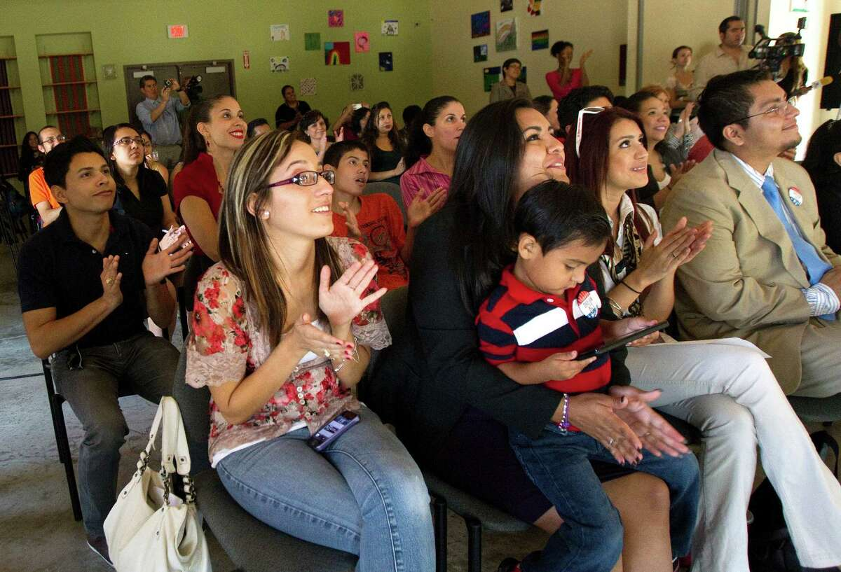 Thailandia Alaffita, front left, cheers the president's address Friday in a crowd at Houston's Baker-Ripley Neighborhood Center.