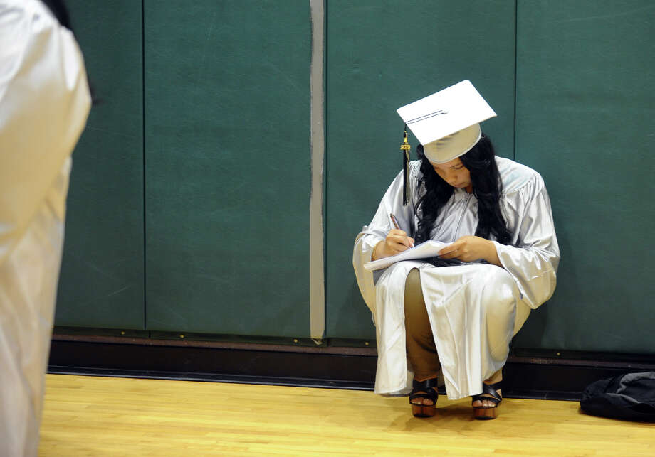 Graduate Krystina Polchies signs a classmate's yearbook before the start of Bridge Academy's Class of 2012 Commencement Exercises in Bridgeport, Conn. on Friday June 15, 2012. Photo: Christian Abraham / Connecticut Post