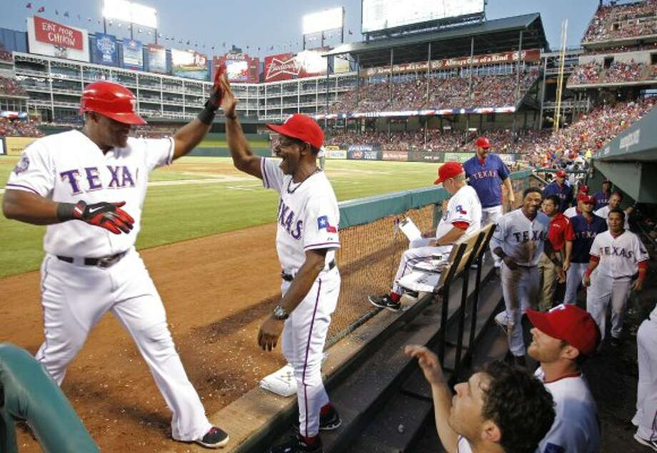 Adrian Beltre, left, arrives at the dugout, greeted by manager Ron Washington, after scoring on a two-run single by David Murphy in the fifth inning.  (Paul Moseley / McClatchy-Tribune News Service)