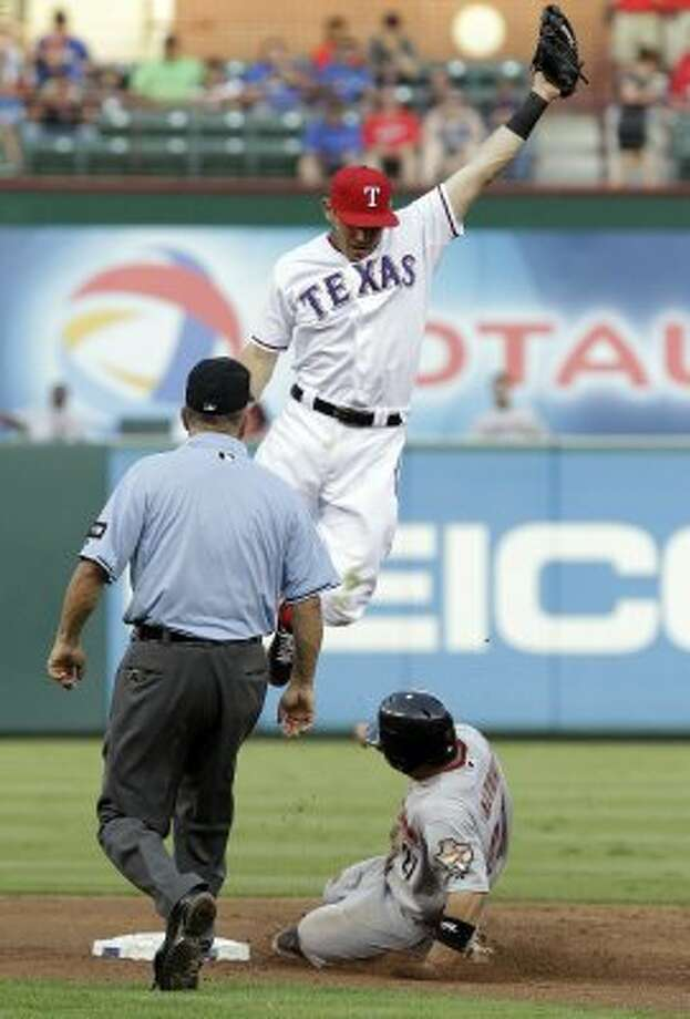 Jose Altuve, bottom right, steals second base as Ian Kinsler, top, leaps and umpire Dale Scott looks on during the third inning. (LM Otero / Associated Press)