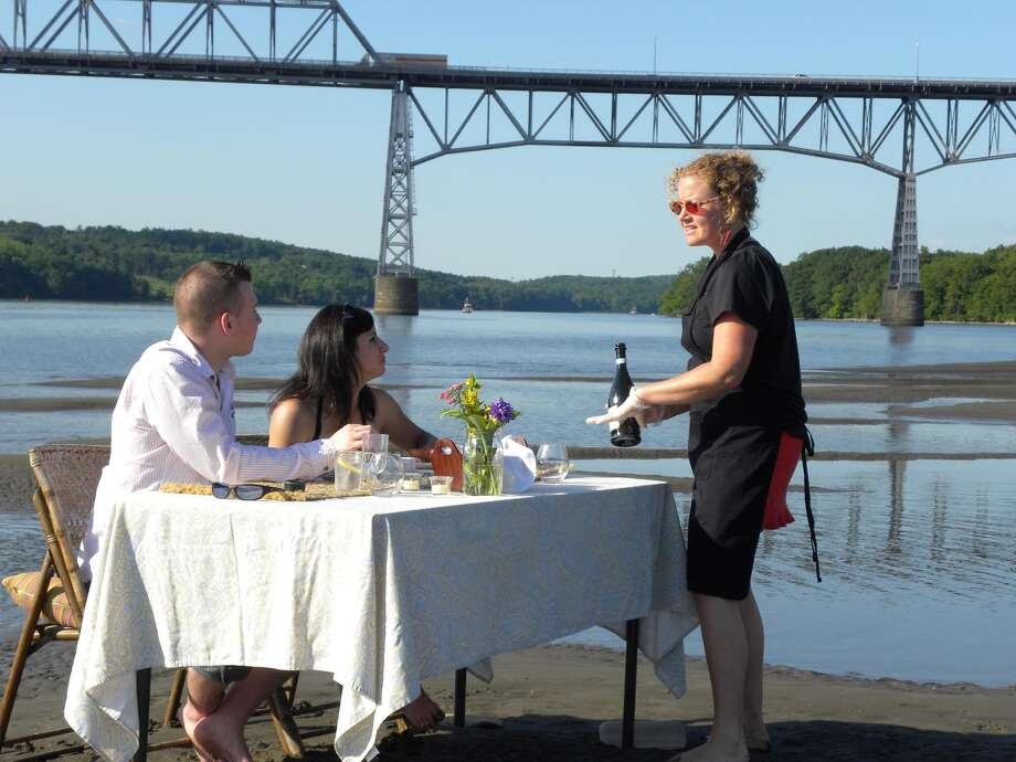 Liz Beals of Stuyvesant, Columbia County, and James Maston of Pittsfield, Mass., have a dinner date on a sandbar in the Hudson River south of the Rip Van Winkle Bridge on Thursday evening, June 14. the sandbar was the site of a dinner catered for the couple by The Chefs Consortium, a group of local-food advocates of which Beals is a member. Consortium chef Noel Conklin catered and served the meal. (Steve Barnes / Times Union)