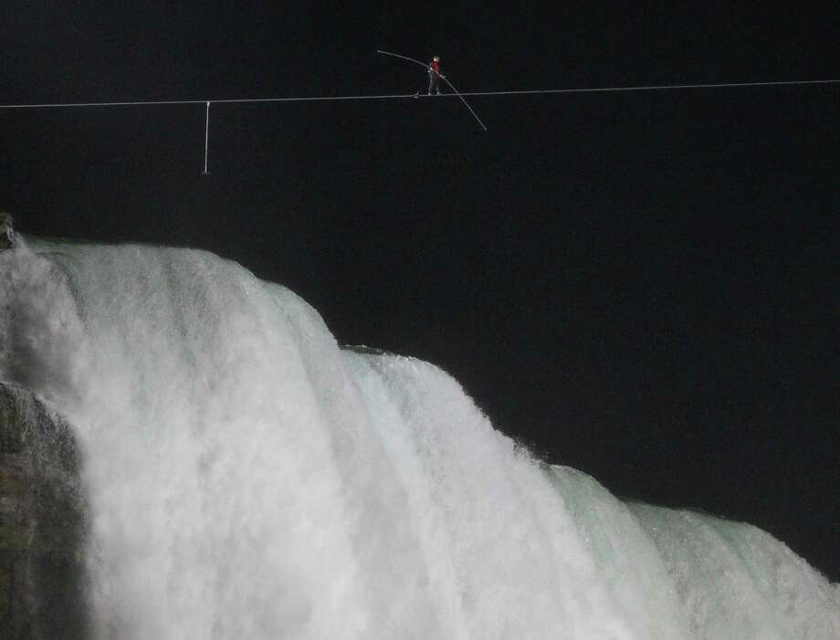 Nik Wallenda walks across Niagara Falls on a tightrope as seen from Niagara Falls, N.Y., Friday, June 15, 2012. Wallenda has finished his attempt to become the first person to walk on a tightrope 1,800 feet across the mist-fogged brink of roaring Niagara Falls. The seventh-generation member of the famed Flying Wallendas had long dreamed of pulling off the stunt, never before attempted. Photo: AP