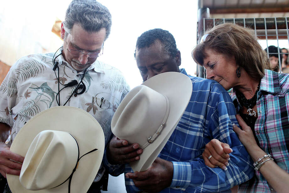 Michael Cotugno, one of the benefit coordinators, (from left), barrel man and rodeo clown Leon Coffee and his wife Terri Coffee pray during the Buck up for Leon benefit held Friday June 15, 2012 at Tejas Rodeo Arena in Bulverde, Tx. Tejas Rodeo will host events Friday and Saturday to raise funds to offset medical expenses for Coffee, who contracted spinal meningitis after spine surgery in March. Photo: Edward A. Ornelas, San Antonio Express-News / © 2012 San Antonio Express-News