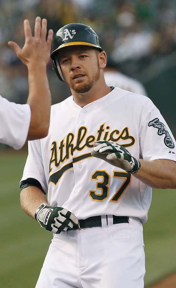 Oakland Athletics Brandon Moss is greeted at the plate after hitting a two-run home run against the San Diego Padres during first inning of a baseball game in Oakland, Calif., Friday, June 15, 2012. (AP Photo/George Nikitin) Photo: George Nikitin, Associated Press