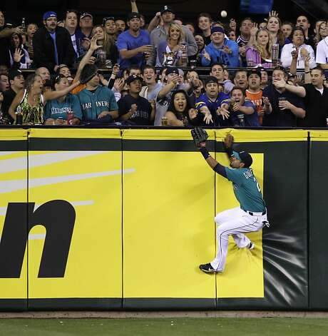 Seattle Mariners center fielder Franklin Gutierrez tries to hold on after he climbed the wall early trying to catch a two-run home run hit by San Francisco Giants' Melky Cabrera in the eighth inning of an MLB baseball game, Friday, June 15, 2012, in Seattle. (AP Photo/Ted S. Warren) Photo: Ted S. Warren, Associated Press