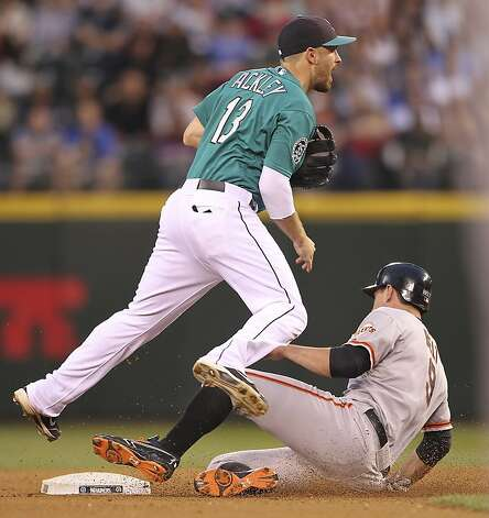 SEATTLE, WA - JUNE 15:  Dustin Ackley #13 of the Seattle Mariners turns a double play over Brandon Belt #9 of the San Francisco Giants at Safeco Field on June 15, 2012 in Seattle, Washington. (Photo by Otto Greule Jr/Getty Images) Photo: Otto Greule Jr, Getty Images