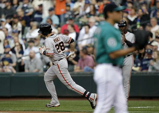 San Francisco Giants' Buster Posey, left, rounds the bases as Seattle Mariners pitcher Jason Vargas stands on the mound at right after Posey hit a solo home run in the second inning of a baseball game, Friday, June 15, 2012, in Seattle. (AP Photo/Ted S. Warren) Photo: Ted S. Warren, Associated Press