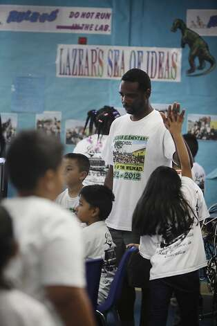 Lazear Elementary School principal Kareem Weaver (standing) gives high fives to students after they've finished their reading test on Wednesday, June 13, 2012 in Oakland, Calif. Photo: Lea Suzuki, The Chronicle