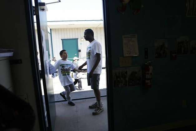Lazear Elementary School principal Kareem Weaver (right) talks with Jose Pelayo (left) before taking a reading test on Wednesday, June 13, 2012 in Oakland, Calif. Photo: Lea Suzuki, The Chronicle
