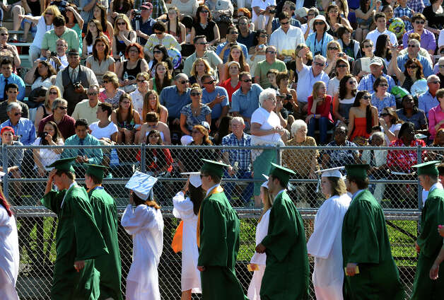 As friends and family look on, graduates walk out onto the football field at the start of Norwalk High School's Class of 2012 Commencement Ceremony in Norwalk, Conn. on Friday June 15, 2012. Photo: Christian Abraham