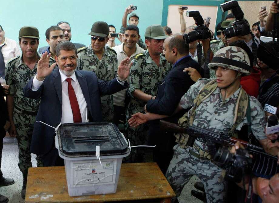 Egyptian presidential candidate Mohammed Morsi waves after he casts his vote at a polling station in Zagazig, 63 miles (100 kilometers) northeast of Cairo, Egypt, Saturday, June 16, 2012. Egyptians voted Saturday in the country's landmark presidential runoff, choosing between Hosni Mubarak's ex-prime minister and an Islamist candidate from the Muslim Brotherhood after a race that has deeply polarized the nation. The two-day balloting will produce Egypt's first president since a popular uprising last year ousted Mubarak, who is now serving a life sentence. Photo: Amr Nabil, Associated Press