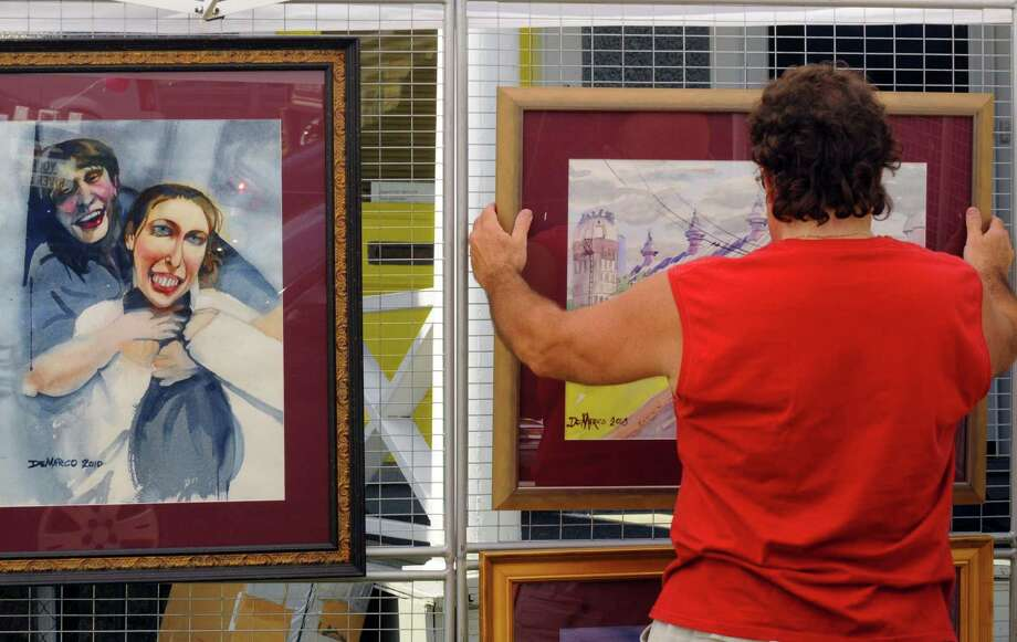 Artist Charles Demarco hangs his work for display during the Upper Union Street Strawberry Fest and Art Show in Schenectady  N.Y. Saturday June 16, 2012. (Michael P. Farrell/Times Union) Photo: Michael P. Farrell