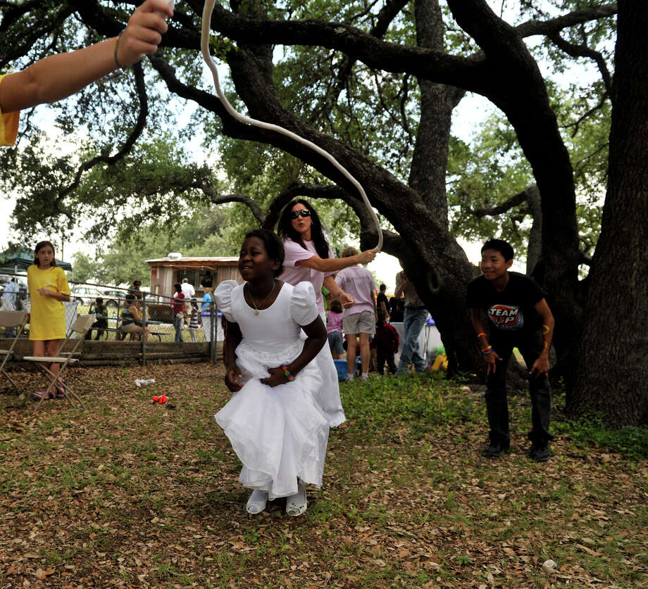 Patricia Kamanani jumps rope as Leslie Greehy turns the rope and Ring Ted looks on  during World Refugee Day activities at St. Francis Episcopal church Saturday. Photo: Robin Jerstad, Robin Jerstad/For The Express-News / Robin Jerstad