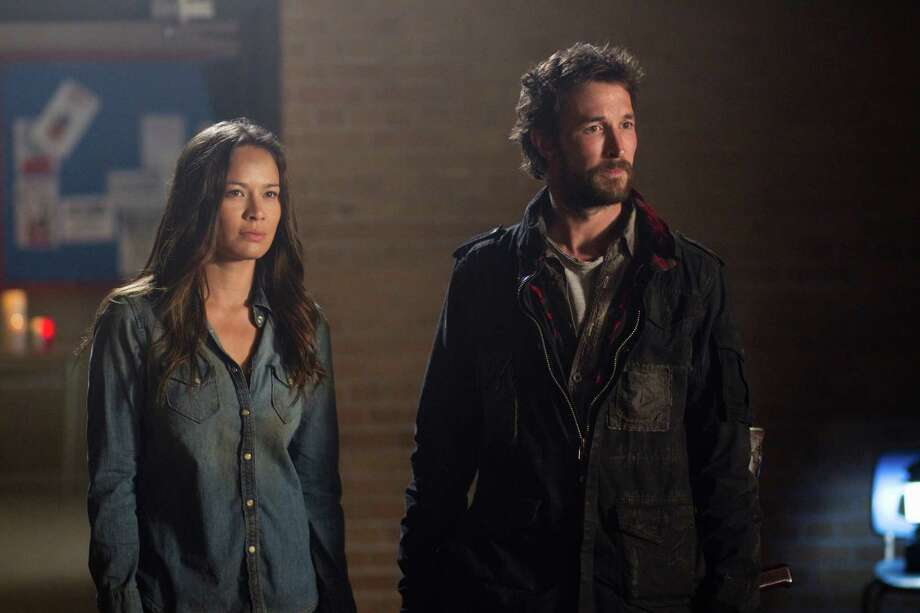 "In this undated photo released by TNT, actors, Moon Bloodgood, left, and Noah Wyle, appear in a scene from TNT's ""Falling Skies"" Season Finale - Part 1: ""Mutiny."" Wyle is confronting an alien invasion, the death of his wife and the potential annihilation of the human species in the new season of ""Falling Skies,"" which debuts Sunday, June 17, 2012, 9-11 p.m. EDT on TNT.  (AP Photo/TNT, Ken Woroner) Photo: Ken Woroner"