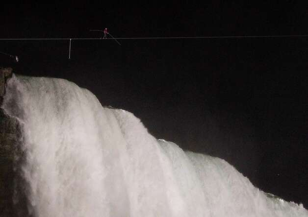 Nik Wallenda walks across Niagara Falls on a tightrope as seen from Niagara Falls, N.Y., Friday, June 15, 2012. Wallenda has finished his attempt to become the first person to walk on a tightrope 1,800 feet across the mist-fogged brink of roaring Niagara Falls. The seventh-generation member of the famed Flying Wallendas had long dreamed of pulling off the stunt, never before attempted. (AP Photo/James P. McCoy) Photo: James P. McCoy