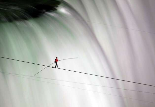 Nik Wallenda walks over Niagara Falls on a tightrope in Niagara Falls, Ontario, on Friday, June 15, 2012. Wallenda has finished his attempt to become the first person to walk on a tightrope 1,800 feet across the mist-fogged brink of roaring Niagara Falls. The seventh-generation member of the famed Flying Wallendas had long dreamed of pulling off the stunt, never before attempted. (AP Photo/The Canadian Press, Frank Gunn) Photo: Frank Gunn