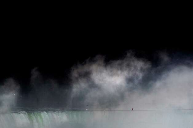 Nik Wallenda walks a tightrope over Niagara Falls as seen from Niagara Falls, Ontario, on Friday, June 15, 2012. Wallenda has finished his attempt to become the first person to walk on a tightrope 1,800 feet across the mist-fogged brink of roaring Niagara Falls. The seventh-generation member of the famed Flying Wallendas had long dreamed of pulling off the stunt, never before attempted. (AP Photo/The Canadian Press, Nathan Denette) Photo: Nathan Denette