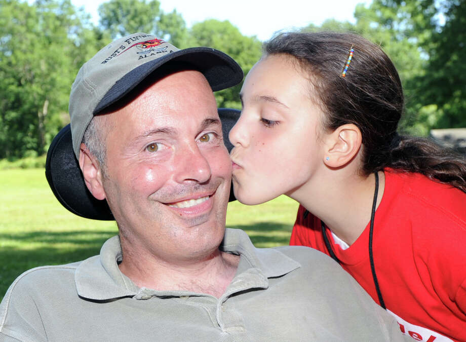 Sydney Petrone, 9, a fourth-grade student at North Street School in Greenwich, kisses her father Roger Petrone during a fundraiser Sydney organized for those living with Lou Gehrig's disease, also known as ALS, at Camp Simmons in Greenwich, Saturday, June 16, 2012. Roger Petrone, a Greenwich police officer, has ALS, or amyotrophic lateral sclerosis, which is a degenerative disease of the nerve cells in the brain and spinal cord that causes weakness and atrophy of the muscles throughout the body. Photo: Bob Luckey / Greenwich Time