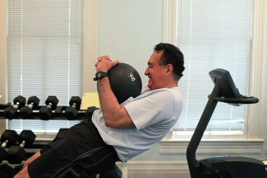 Henry Cisneros does his core routine as he exercises at his home on Tuesday, June 12, 2012. He alternates cardio and weights to exercise most days of the week.