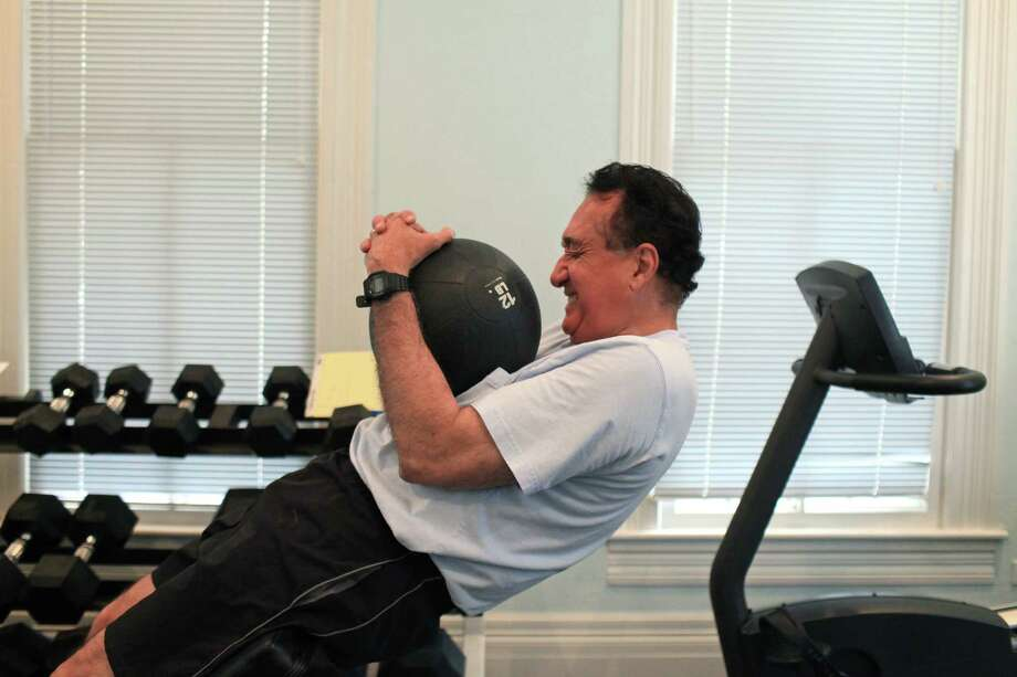 Henry Cisneros does his core routine as he exercises at his home on Tuesday, June 12, 2012. He alternates cardio and weights to exercise most days of the week. Photo: Lisa Krantz, San Antonio Express-News / 2012 San Antonio Express-News