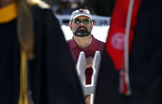 Rick Strickland watches graduates walk into Buck Shaw stadium for Santa Clara University commencement exercises in Santa Clara, Calif. on Saturday, June 16, 2012. Four engineeering students are continuing the alternative energy research that Strickland's son Dan was working on before his death in an auto accident last year. Photo: Paul Chinn, The Chronicle