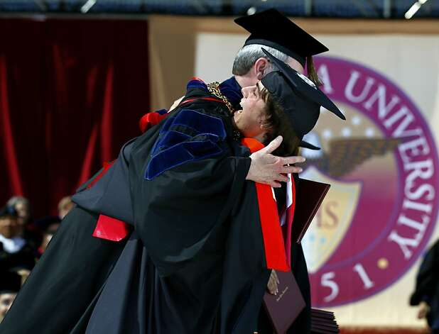 Engineering graduate Mike Sizemore bear hugs Santa Clara University President Michael Engh at the commencement ceremony in Santa Clara, Calif. on Saturday, June 16, 2012. Sizemore is among a group of students continuing the research in alternative energy that their associate professor, Dan Strickland, was working on before he died in an auto accident last year. Photo: Paul Chinn, The Chronicle