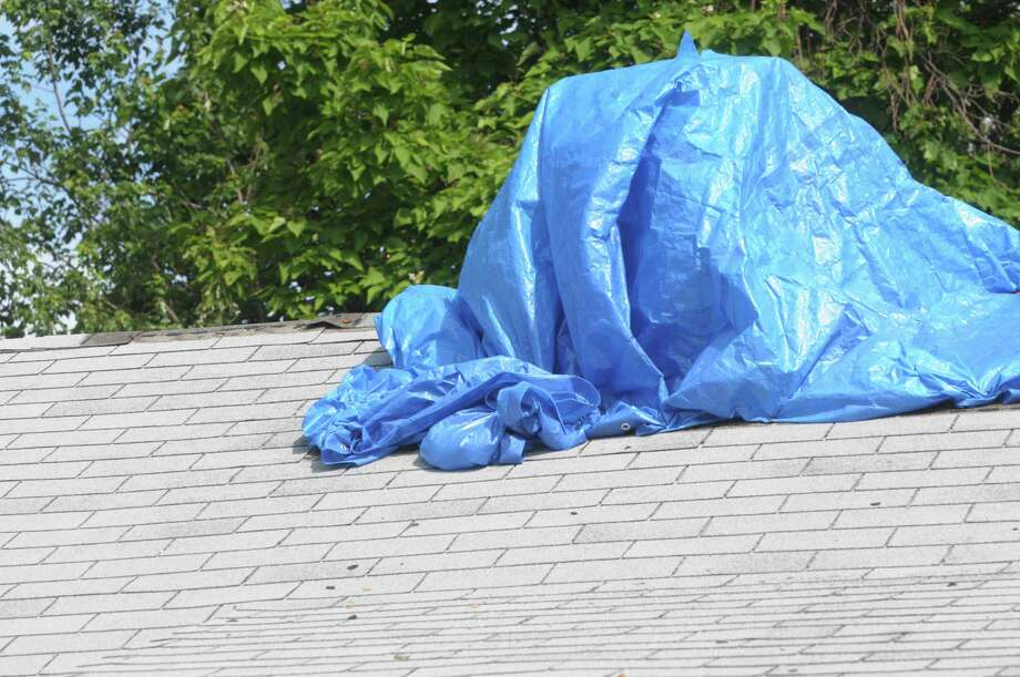 A view of the roof at the home of Susan Browne of Colonie on Thursday, June 14, 2012,  after a roofer started to do what she said was unauthorized work on her roof.  The blue tarp covers up an area around the chimney where the roofer removed shingles.    (Paul Buckowski / Times Union) Photo: Paul Buckowski / 00018090A