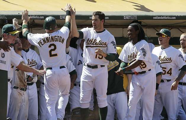 Oakland Athletics' Cliff Pennington (2) is congratulated by teammates after scoring on a wild pitch by San Diego Padres' Luke Gregerson during the seventh inning of a baseball game in Oakland, Calif., Saturday, June 16, 2012. The Athletics won 6-4. (AP Photo/Jeff Chiu) Photo: Jeff Chiu, Associated Press