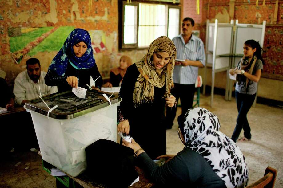 Egyptian women vote at a polling station in Shubrah El-Kheima, a working class, industrial area on the outskirts of Cairo, Egypt on Saturday, June 16, 2012. Egyptians voted Saturday in the country's landmark presidential runoff, choosing between Hosni Mubarak's ex-prime minister and an Islamist candidate from the Muslim Brotherhood after a race that has deeply polarized the nation. The two-day balloting will produce Egypt's first president since a popular uprising last year ousted Mubarak, who is now serving a life sentence. Photo: Pete Muller, Associated Press / AP
