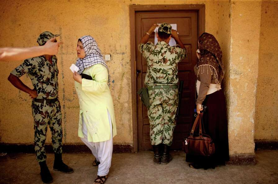 Egyptian soldiers help female voters locate their names of registration lists at a polling station i