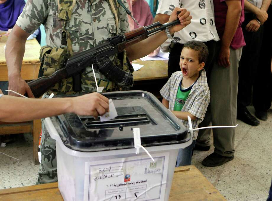 An Egyptian boy yawns as he watches a voter cast his ballot at a polling station in Zagazig, 63 miles (100 kilometers) northeast of Cairo, Egypt, Saturday, June 16, 2012. Photo: Amr Nabil, Associated Press / AP