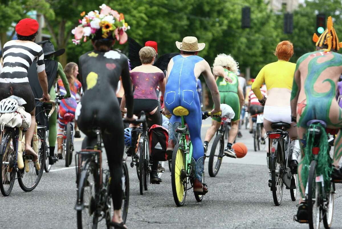 Bicyclists make their way from a pre-parade paint party in Ballard to the parade route in Fremont..
