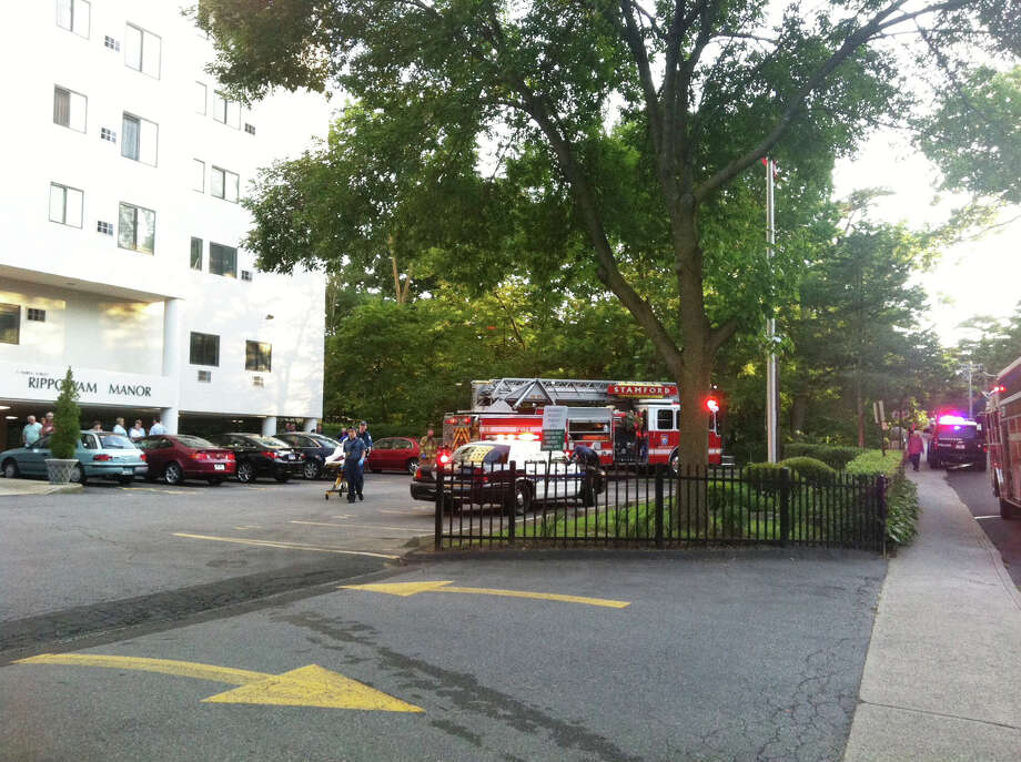 Emergency personnel respond to a report of a child who fell six stories from an apartment at Rippowam Manor at 11 W. North St. in downtown Stamford around 7:30 p.m. Saturday. Photo: Kate King