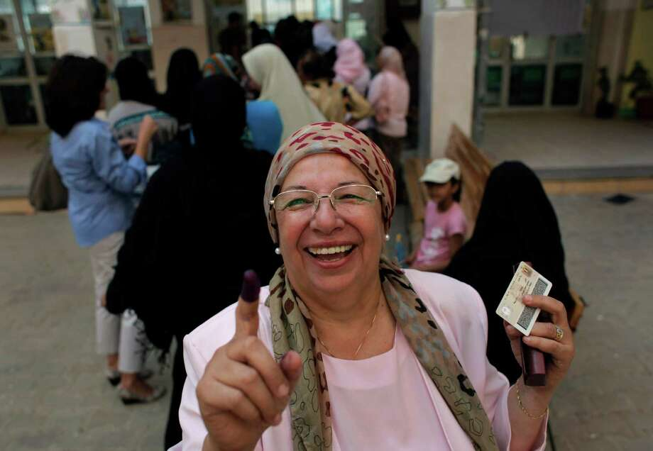 An Egyptian woman shows her ink-stained finger after voting, while others line up in front of their polling station during the first day of the presidential runoff, in Cairo, Egypt, Saturday, June 16, 2012. Egyptians voted Saturday in the country's landmark presidential runoff, choosing between Hosni Mubarak's ex-prime minister and an Islamist candidate from the Muslim Brotherhood after a race that has deeply polarized the nation. The two-day balloting will produce Egypt's first president since a popular uprising last year ousted Mubarak, who is now serving a life sentence. (AP Photo/Nasser Nasser) Photo: Nasser Nasser