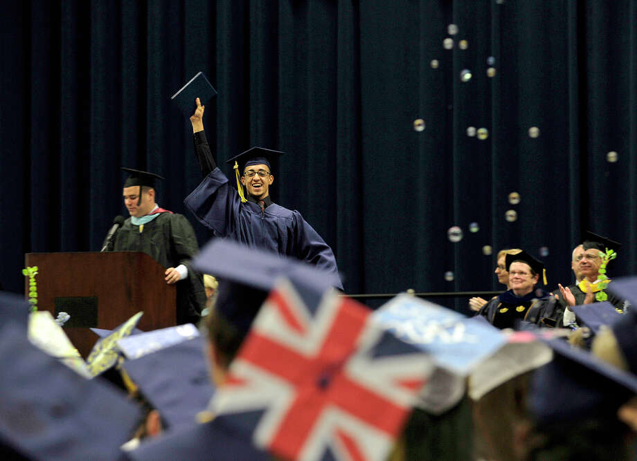 Karim Abdelkader raises his diploma after receiving it on stage during the Brookfield High School graduation in the O'Neill Center at Western Connecticut State University's westside campus in Danbury on Saturday, June 16, 2012. Photo: Jason Rearick / The News-Times