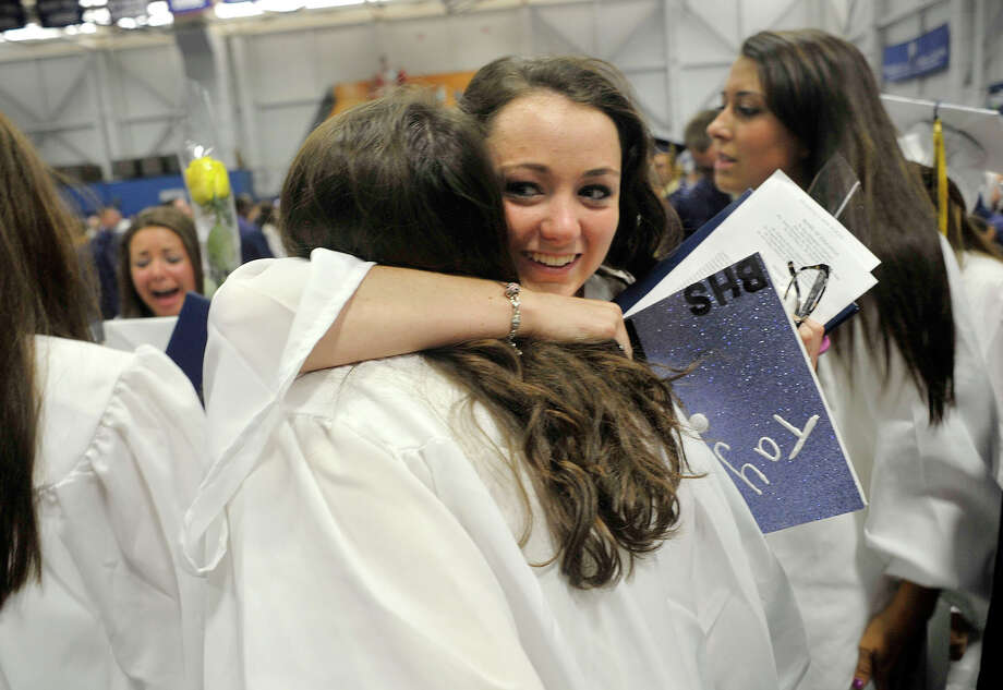 Leanna Thomas, left, hugs Taylor Ryan following the Brookfield High School graduation in the O'Neill Center at Western Connecticut State University's westside campus in Danbury on Saturday, June 16, 2012. Photo: Jason Rearick / The News-Times