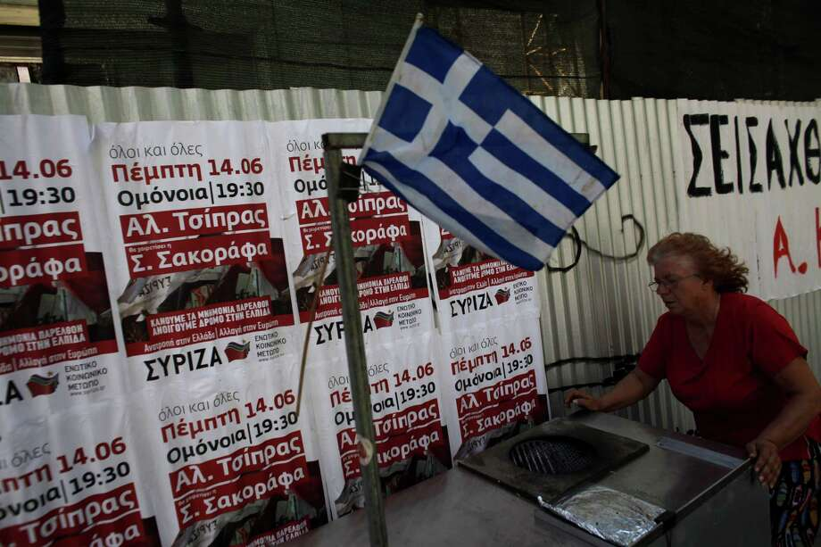 Maria, 61, a street vendor of corn-on-the-cob (surname not given) pushes her cart in front of election posters of radical left party (SYRIZA) one day before general elections in Athens, Saturday, June 16, 2012. Greeks vote for the second time in six weeks Sunday amid fears that the country could be forced out of the euro if they reject the strict austerity measures taken in return for billions of euros in rescue loans from other European countries and the International Monetary Fund. (AP Photo/Kostas Tsironis) Photo: Kostas Tsironis