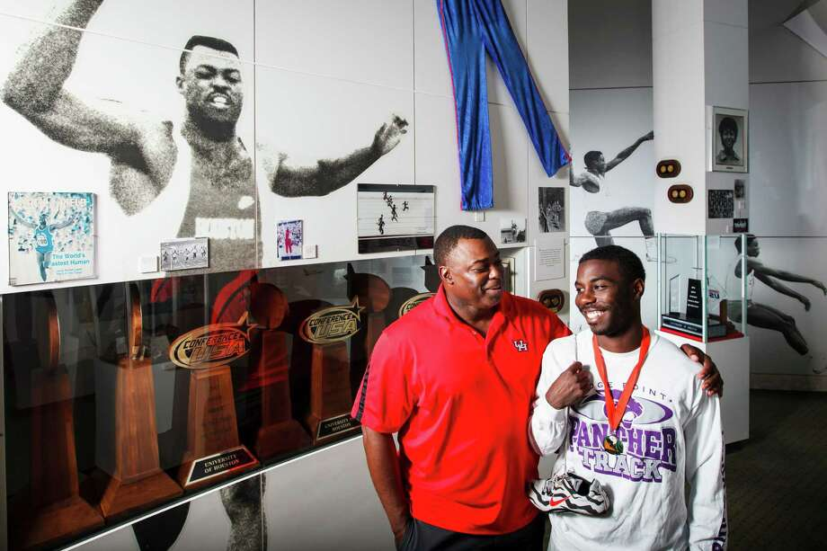University of Houston track coach Leroy Burrell, left, and his son Cameron, who won the state 100-meter title for Ridge Point, pose for a photo in front of a giant photo of Leroy Burrell running track during his youth at the U of H Cougar Hall of Fame, Wednesday, June 13, 2012, in Houston.  Leroy held the world record in the 100 meter dash on two separate occasions during his track and field career.   ( Michael Paulsen / Houston Chronicle ) Photo: Michael Paulsen / © 2012 Houston Chronicle