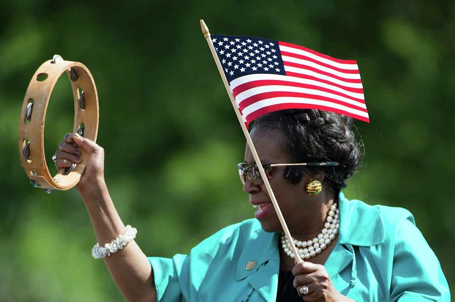 U.S. Rep. Sheila Jackson Lee waves a flag and shakes a tambourine as she rides in the 39th Annual Juneteenth Parade on Saturday, June 16, 2012, in Houston. News: Jackson Lee's entitlements comment riles conservatives Photo: Smiley N. Pool, Houston Chronicle / © 2012  Houston Chronicle