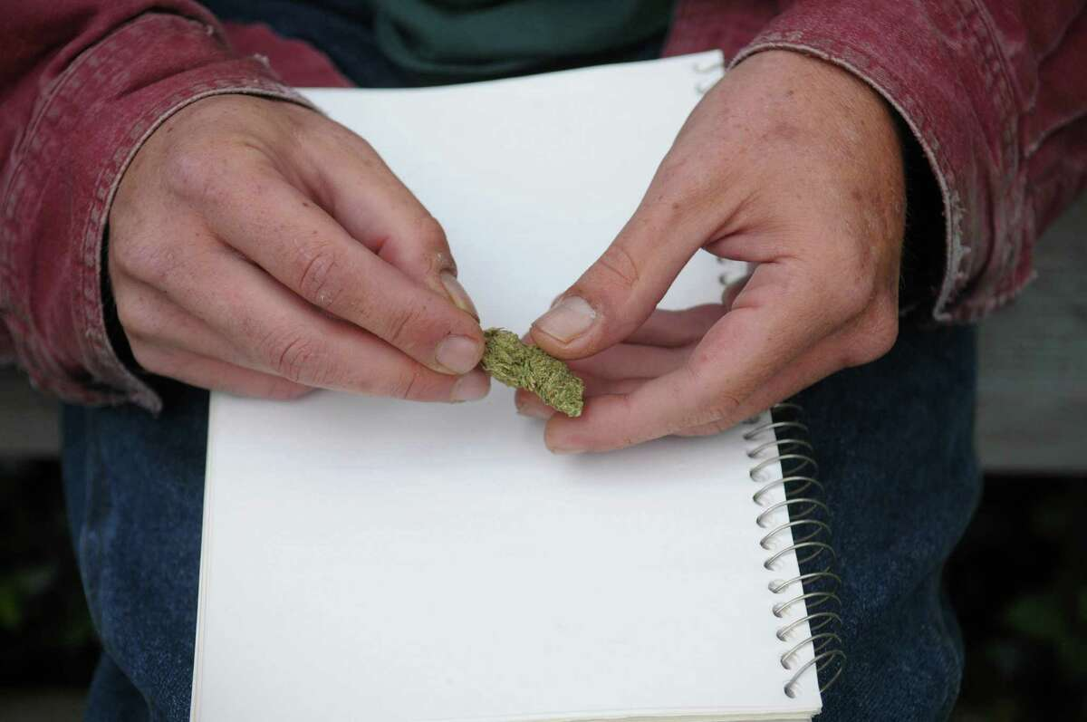 Kevin Jones, director of the New York Capital Region chapter of NORML, breaks up some dried cannabis before rolling it into a cigarette outside where he lives on Monday, June 4, 2012 in Salem, NY. (Paul Buckowski / Times Union)