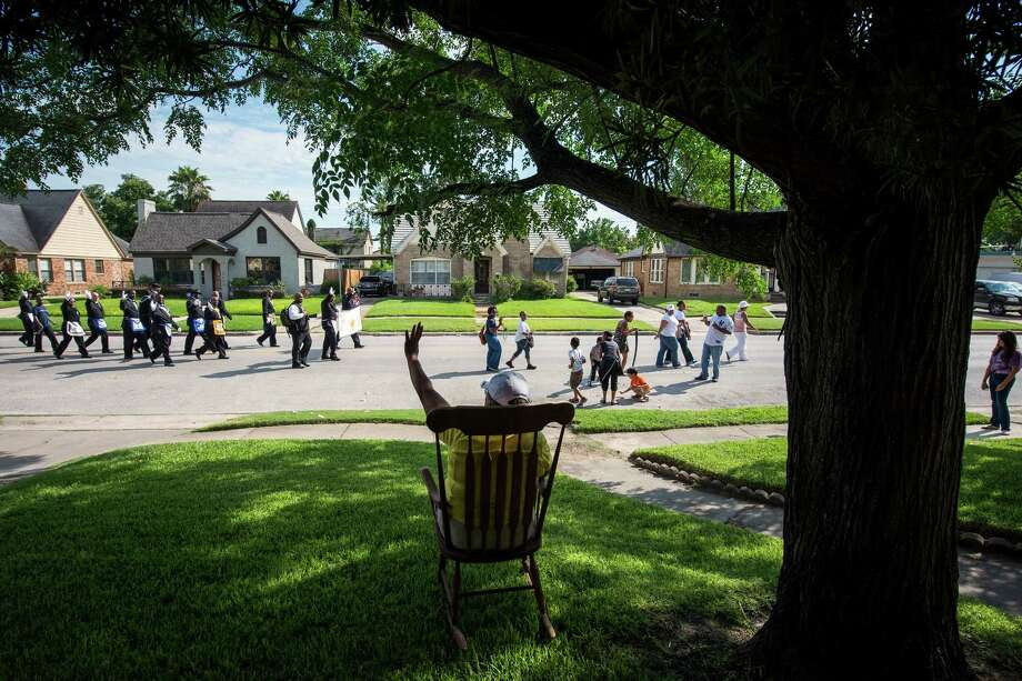 Jewell Bass sits in her front yard on Wheeler on Saturday while the 39th annual Juneteenth parade, founded by the National Emancipation Association, passes by. The parade was one of many around the area. Photo: Smiley N. Pool / © 2012  Houston Chronicle
