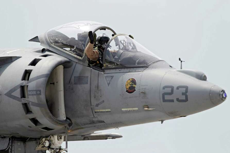 The pilot of a Marine AV-8 Harrier waves to the crowd after a combat demonstration at Burke Lakefron