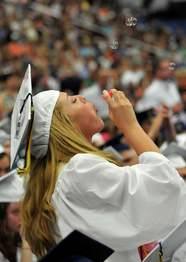 Francesca Pugliese blows bubbles during the Brookfield High School graduation in the O'Neill Center at Western Connecticut State University's westside campus in Danbury on Saturday, June 16, 2012. Photo: Jason Rearick / The News-Times